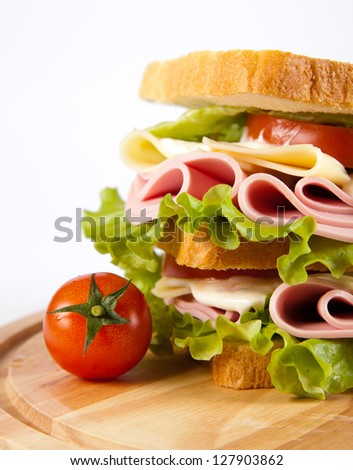 big sandwich with fresh vegetables on wooden board on white background - stock photo