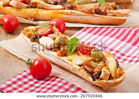 Big sandwich with roasted vegetables (zucchini, eggplant, tomatoes) and chicken with cheese and basil on old wooden background - stock photo