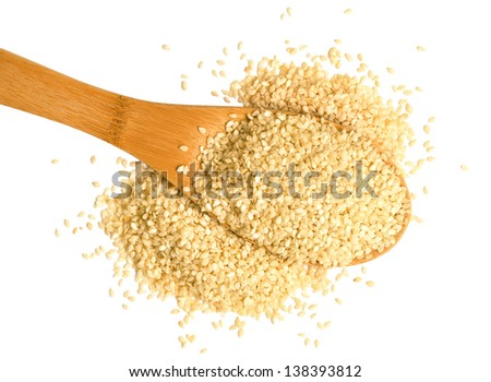 Big scoop of sesame seeds over a white background.