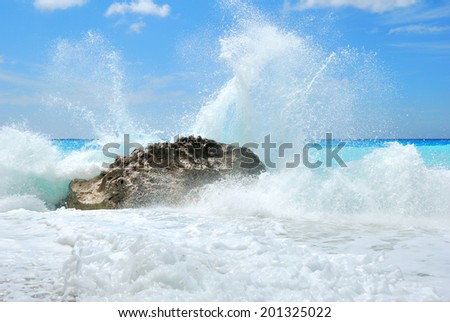 Big sea wave breaking on the shore rocks with a high clean sea spray - stock photo