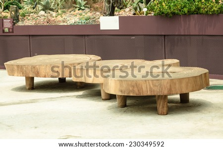 Big seat chairs made of wood trunk stumps at waiting area in park - stock photo