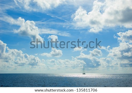 Big sheep with the sails down is drifting in the Mediterranean sea on the background of beautiful blue sky with white clouds.