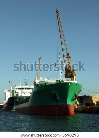 Big ship unloading in dock - stock photo