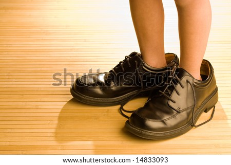 Big shoes to fill, child's feet in large grown-up black shoes, on backlit wood floor, playing dress-up - stock photo