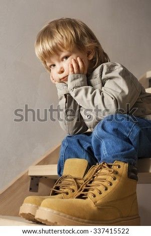 Big shoes to fill, child's feet in large shoe - stock photo