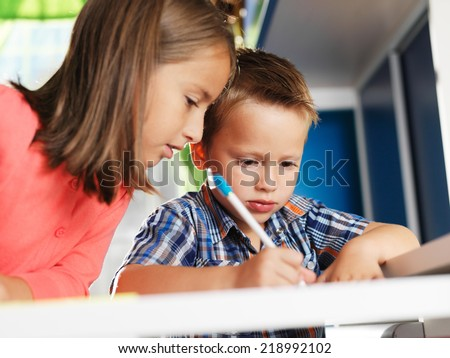 big sister helping little brother with homework - stock photo