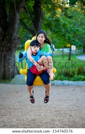 Big sister holding disabled brother on special needs swing at playground in park. Child has cerebral palsy. - stock photo