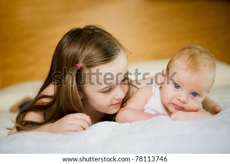 Big sister looks with adoration at little brother - stock photo