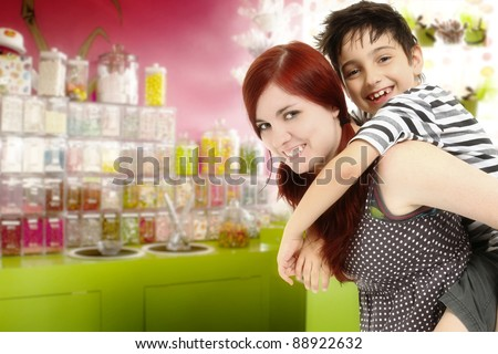 Big sister or babysitter taking younger brother to the candy store. - stock photo