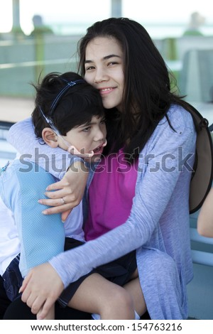 Big sister taking care of disabled little brother, holding him on lap. Child has cerebral palsy. Lesch Nyhan Syndrome. - stock photo