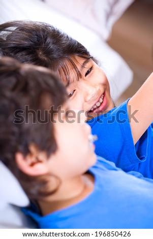 Big sister taking care of her disabled little brother on mat - stock photo