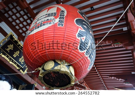 Big  size  red   lantern   in front   of    the  gate  of   Asakusa  area  or   Sensoji   Temple  hang  on  up  to   our    head   with  beautiful   design   and   attracted   people   who  visit. - stock photo
