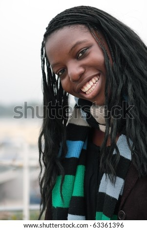 Big smile in spite of foggy day: Cute black teenage girl shows a big smile on a cold foggy day. - stock photo