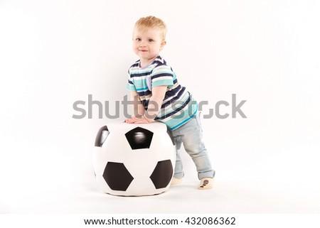 big soccer ball near a little boy - stock photo