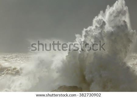 Big splash closeup from a stormy wave breaking against coast rocks. Dark sky before rain and interesting light from a sunbeam filtered by moisture. Soft backlight. - stock photo