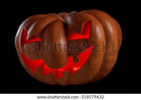 Big spooky halloween pumpkin Jack O Lantern shiny inside on black. Isolated on black background - stock photo