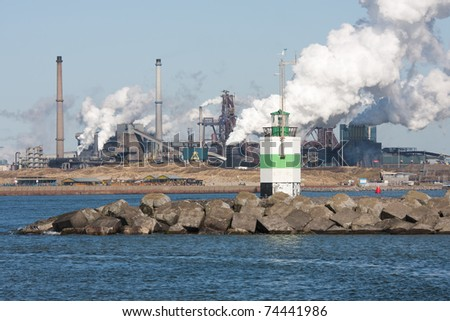 Big steel factory with harbor at the Dutch coast - stock photo