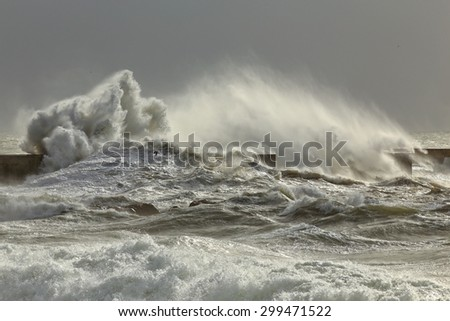 Big stormy sea waves over a pier from the north of Portugal. - stock photo