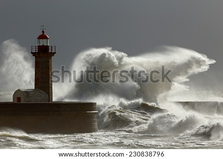 Big stormy waves against lighthouse with interesting light. Porto, Portugal.  Low edition photo. - stock photo