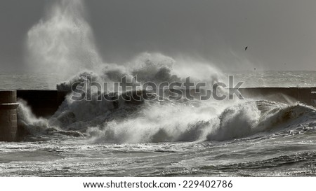 Big stormy waves against pier with interesting light. Porto, Portugal.  - stock photo