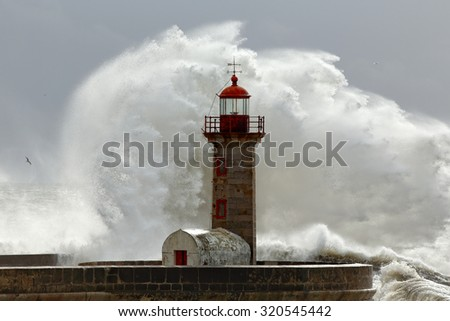 Big stormy waves over old lighthouse and pier of Douro mouth harbor, Porto, Portugal.