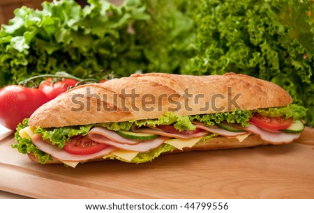 Big sub sandwich with ham and cheese on a wooden cutting board