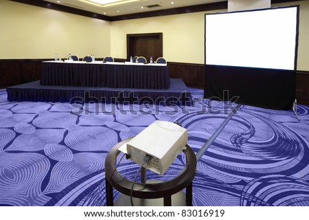 Big table with microphone near screen in bright conference hall, view from projector - stock photo