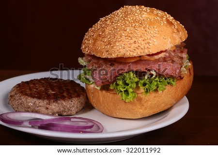 Big tasty appetizing fresh burger of green lettuce red tomato cheese and bacon slice meat cutlet and white bread bun with sesame seeds lying on white plate with cutlet and onion, horizontal picture - stock photo