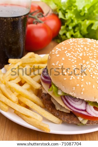 big tasty cheeseburger with french fries and ingredients on a wooden table - stock photo