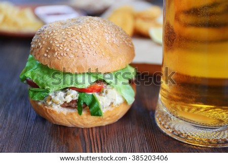 Big tasty hamburger with glass mug of light beer on dark wooden background, close up - stock photo