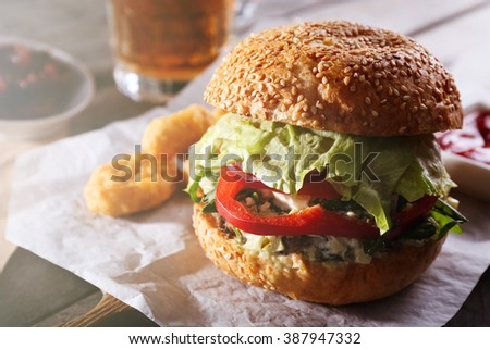 Big tasty hamburger with snacks and glass mug of light beer on wooden table - stock photo