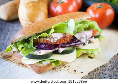 Big tasty sandwich with cheese,ham and vegetables.Selective focus in the middle of sandwich  - stock photo