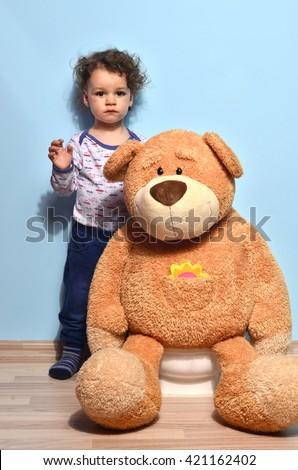Big teddy bear sitting on the potty. Cute kid potty training a teddy bear for pee and poo - stock photo