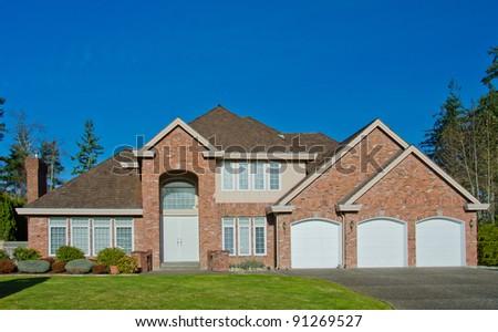 Big, three garage doors, luxury home against dark blue sky - stock photo