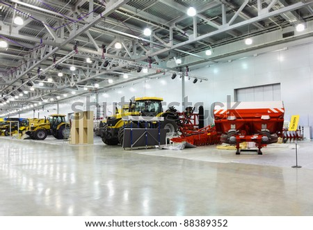 Big tractors are in room at exhibition, special agricultural machines - stock photo
