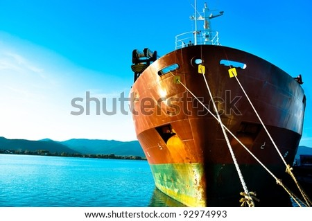 Big transportation boat at the bay against blue sky - stock photo