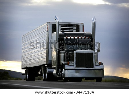 big truck driving on a highway with cloudy sky in background - stock photo