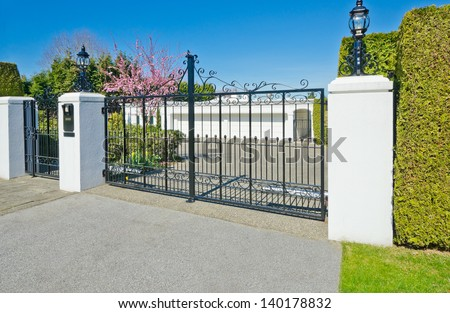 Big two double doors garage with long driveway behind the gates in suburbs of Vancouver, Canada. - stock photo