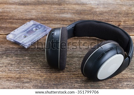 big vintage black headphones on aged wooden background