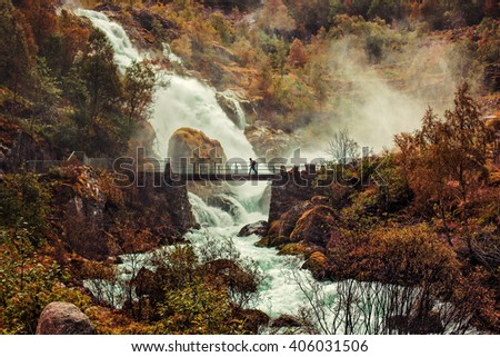 Big waterfall in Norway and man walking on bridge. Autumn red colors - stock photo