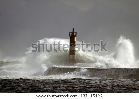 Big wave against lighthouse and pier in the north of Portugal in a stormy overcast evening - mouth of river Ave in Vila do Conde, near Porto - stock photo