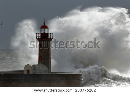 Big wave over old lighthouse, Porto, Portugal - stock photo