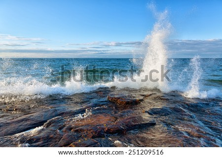 Big Wave Splash on Lake Superior in the Upper Peninsula of Michigan. Waves break against a rocky shoreline near Pictured Rocks National Lakeshore in Munising, Michigan. - stock photo
