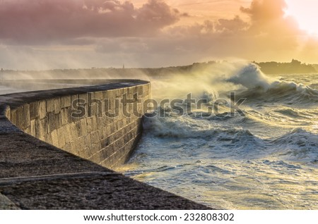 Big waves crushing on curved stone pier, on stormy weather with vivid sunset, big tide, Saint Malo, France. - stock photo