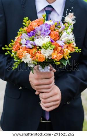 big wedding bouquet in groom hand - stock photo