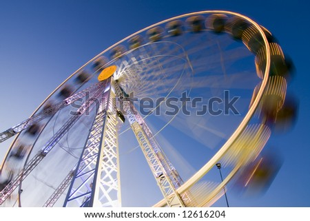Big wheel on a fun fair with colorful lights. Motion blurred. Long exposure time with tripod. - stock photo