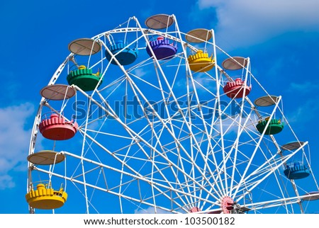 big wheel with multicolored cabins in amusement park - stock photo