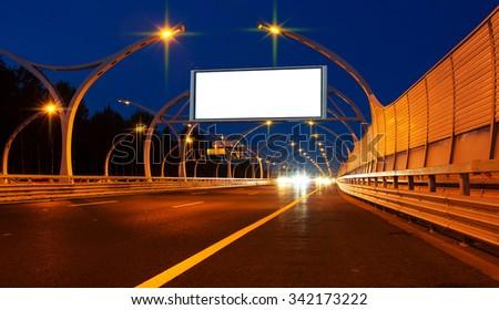 Big white billboard on night highway - stock photo