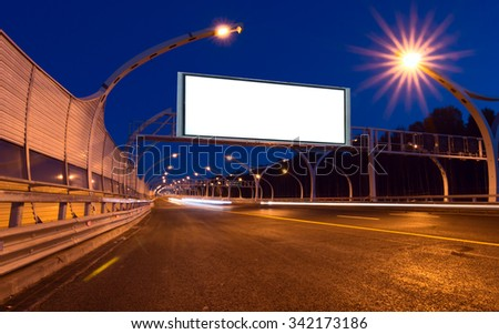 Big white billboard on the night highway - stock photo