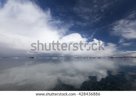 Big white cloud over small snow-covered islands at horizon in Norway - stock photo